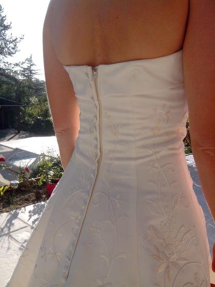 Très belle de robe de mariée blanc satin avec longue traîne. Devant finement brodé.Fermeture dos décorée avec petits boutons nacrés. Excellent état (portée une seule fois !)  Tour de cou amovible. Taille (buste notamment): plutôt 36.  Nettoyée en pressing