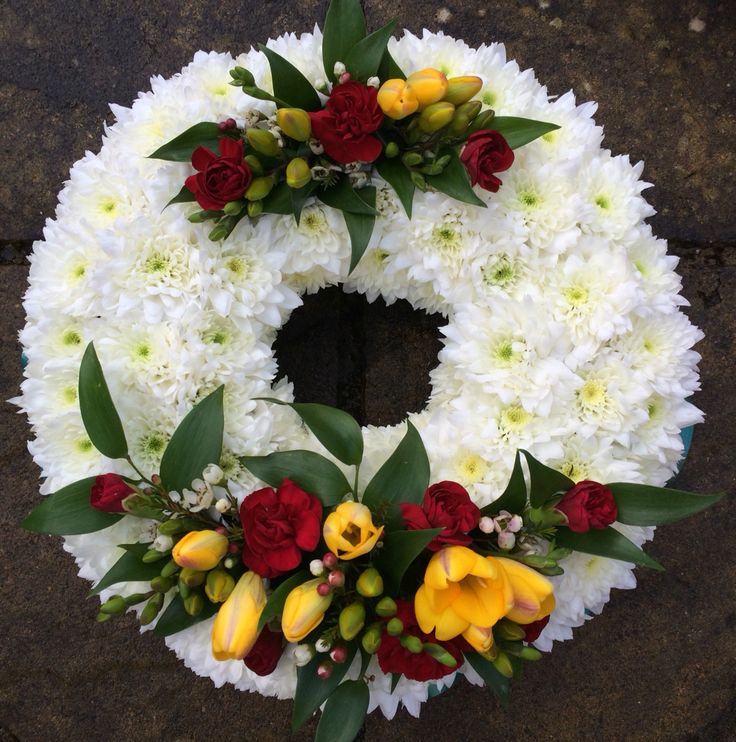 "10"" funeral wreath in vibrant colours using freesias and spray carnations."