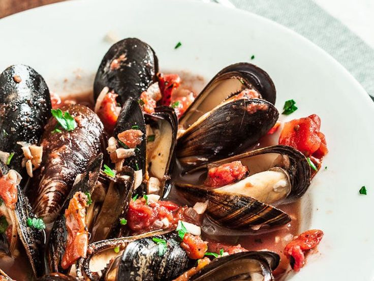 These easy garlic and tomato mussels can be made in minutes to be a fun appetizer or deliciously light seafood dinner.