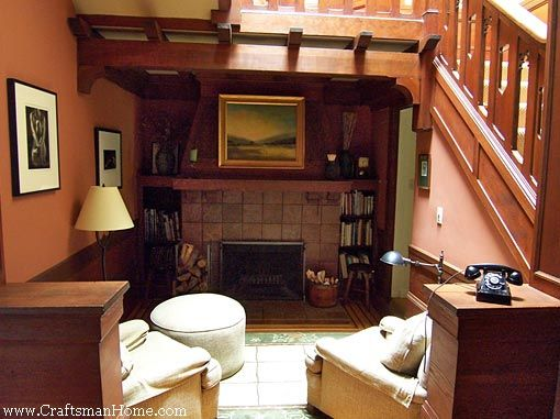 A Bookshelf Flanked Fireplace Tucked Into Sunken Nook Under The Stairs Provides Cozy Conversation Spot Photo Courtesy Of Craftsman Home