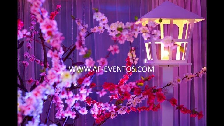 Decoración en el corredor del ingreso del salón con árboles de flores en tonalidades rosa, con faroles de luz cálida rodeando la mesa de dulces para una ambientación especial y stage de fotos