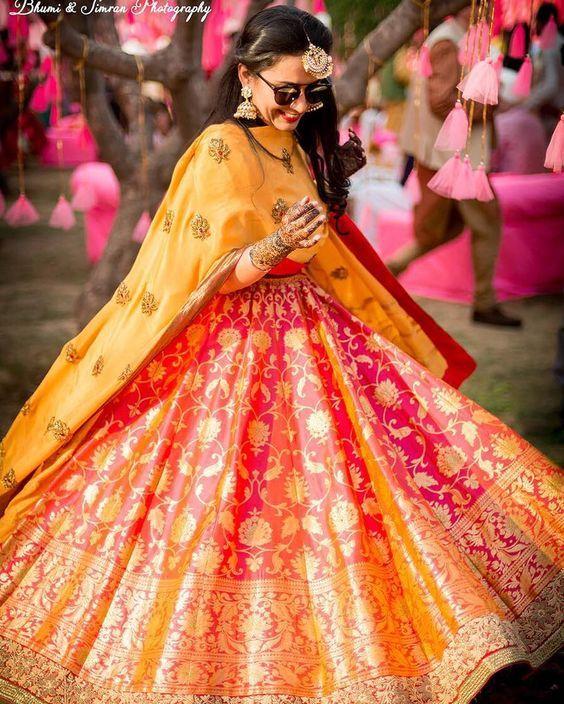 Sangeet Lehengas - Bride in a Benarasi Pink and Orange Lehenga with Yellow Dupatta | WedMeGood #wedmegood #indianbride #indianwedding #bridal #sangeetlehenga #lehenga #benarsi