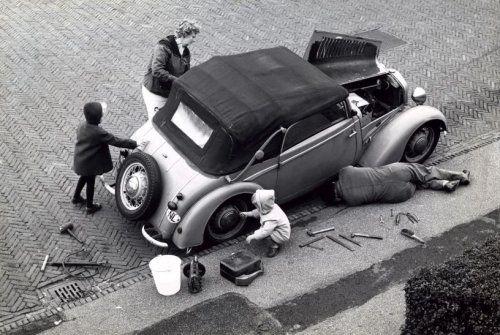 Sleutelen aan de auto op straat.Het hele gezin helpt mee. [1964]
