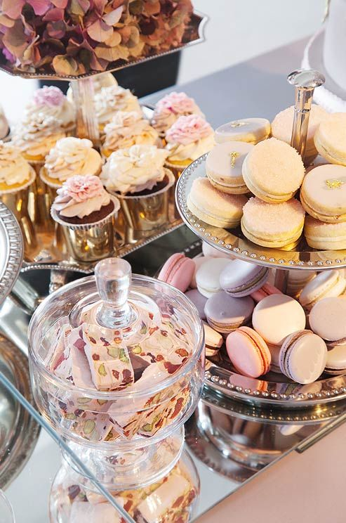 Pistachio-studded nougat, pink and purple macarons and flower- topped cupcakes covered the mirrored dessert table