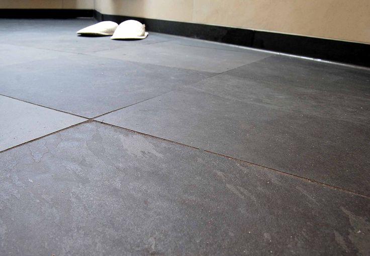 Fußbodenfliesen aus dunkelgrauem Schiefer, im Hintergrund Badewanne und zwei weiße Pantoffeln
