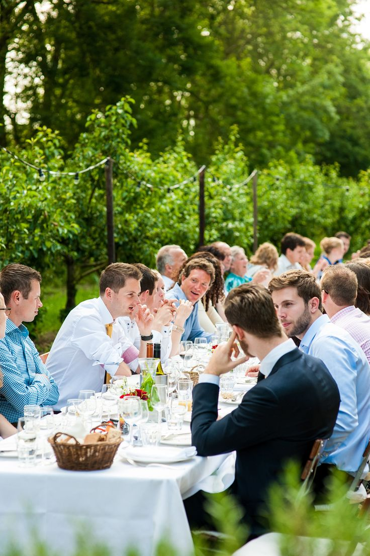 Dineren aan een lange tafel buiten sfeervol in een boomgaard