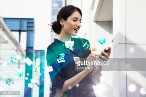 Young businesswoman holding smartphone with apps and icons coming out of it : Stock-Foto
