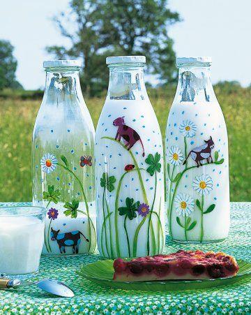 des bouteilles de lait en verre peintes à la peinture vitrail avec des motifs d'herbes, de fleurs des champs, de pâquerettes, de trèfles à quatre feuilles et de mini vaches.