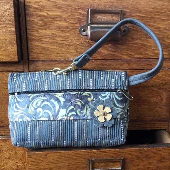 Cute modern color wristlet: gray leather strap, gray and lemon leather flower. Hard-wearing industrial tapestry with a touch of blue and white is accented with a strip of swirly batik fabric  Top zip opens to roomy interior that will fit IPhone 6s+. Theres one inside pocket also big enough for most other phones-or your credit cards. AND theres a clip off key ring!  Outside features one large zip pocket. And that cute flower....  7.5 wide 4.75 deep 1.25 bottom