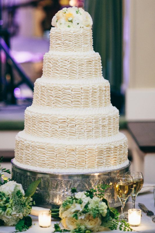 Beautiful wedding cake is crowned by fresh white and cream garden roses and ranunculus. The table is dressed with bridesmaids bouquets and votives.