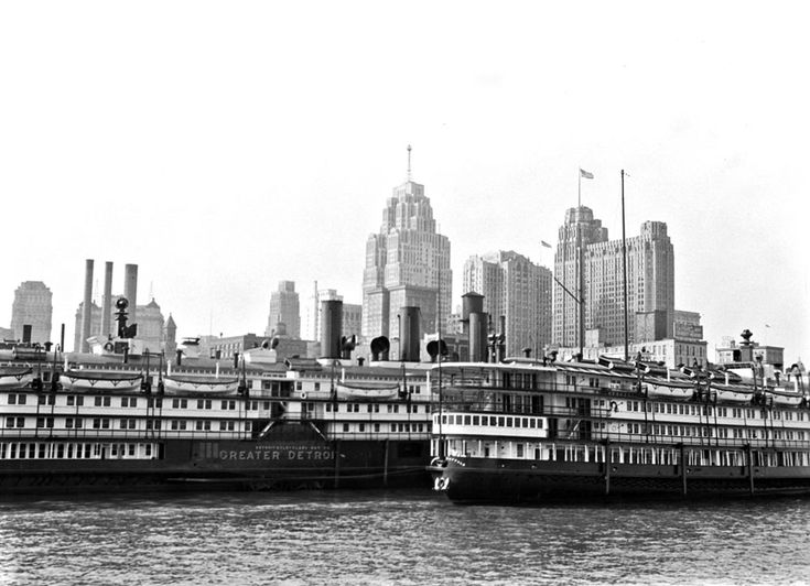 Two passenger boats sit on the Detroit River near downtown Detroit, MI. They likely traveled across Lake Erie between Detroit and Buffalo, NY. The Guardian building is seen flying the American flag on its roof.
