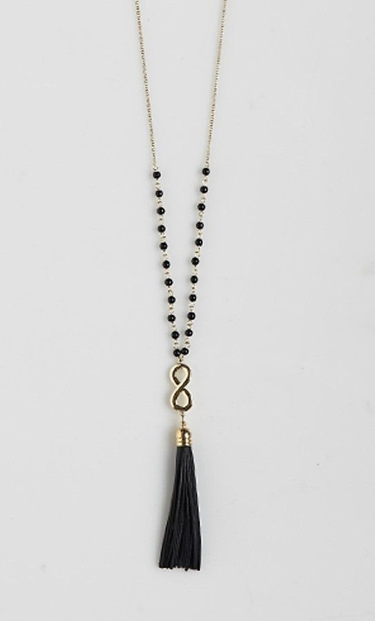 Long chain necklace with bead detailing and a faux leather tassel. Perfect for layering or worn...