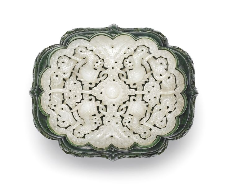 A FINELY CARVED SPINACH-GREEN AND WHITE JADE BOX AND COVER QING DYNASTY, QIANLONG – JIAQING PERIOD of ogival section, the four bracket lobed sides of the box and cover carved in relief with floral blooms among leafy vines, divided into two registers by a lattice concealing the join between the two halves of the container, the domed cover surmounted with a raised multi-lobed border inset with a reticulated plaque of four confronted dragons intertwined with swirling clouds all facing a central…