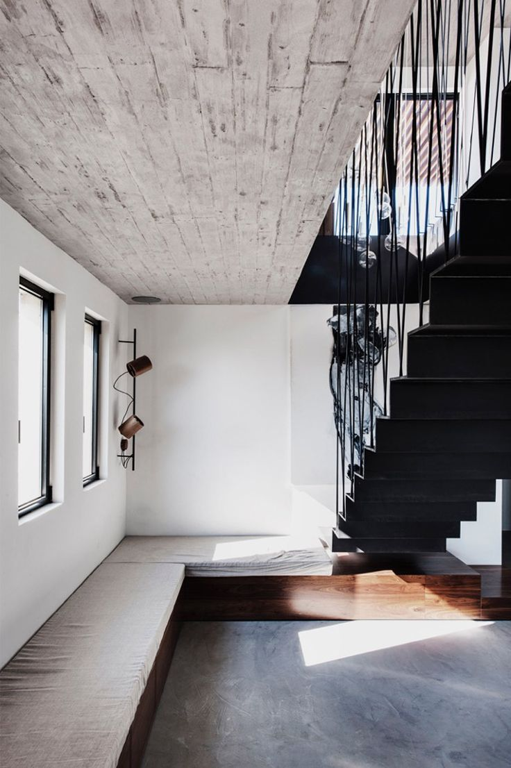 A folded steel staircase supported by criss-crossing rods connects the two levels of this newly renovated duplex apartment in Tel Aviv