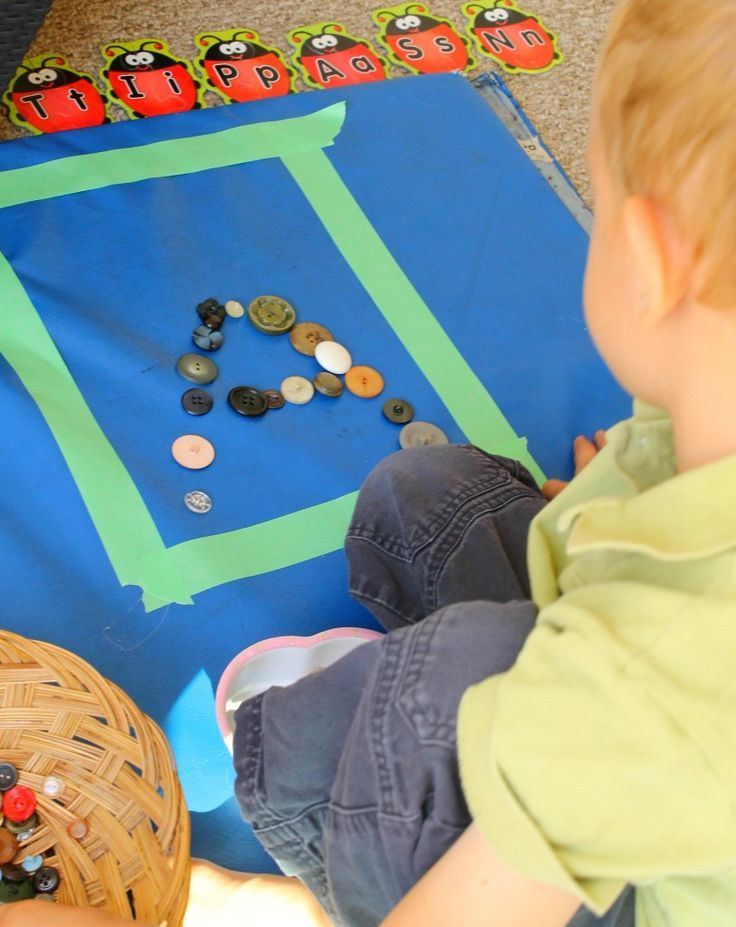 Forming letters out of buttons! A great way to get kids moving and learning with loose parts.