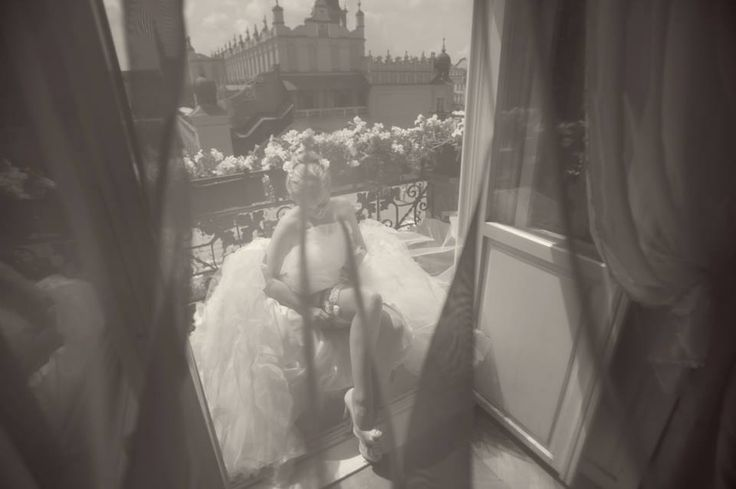 Bride putting on her garter behind sheer curtain on the balcony of the medieval Bonerowski Palace, Krakow, Poland #Cracow#wedding#