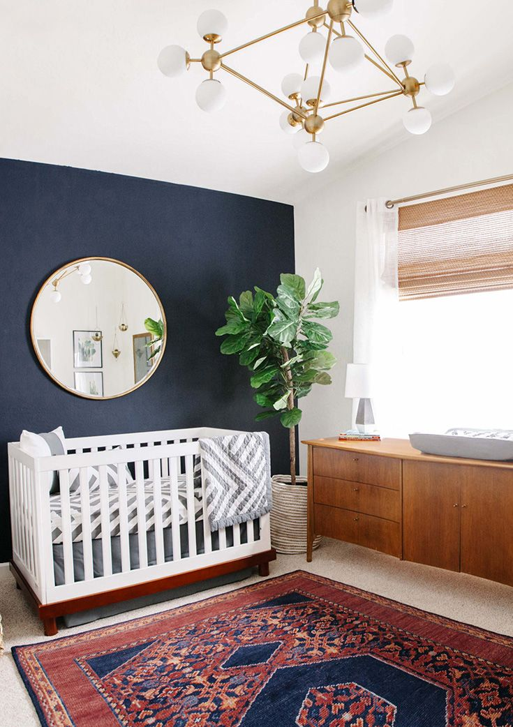 this is a nursery, but still like it for our master (or the idea of it, ha!)   modern brass bubble chandelier with dark navy walls, white crib, gold over-sized mirror, mid-century modern credenza, fiddled fig tree in a bast and boho rug