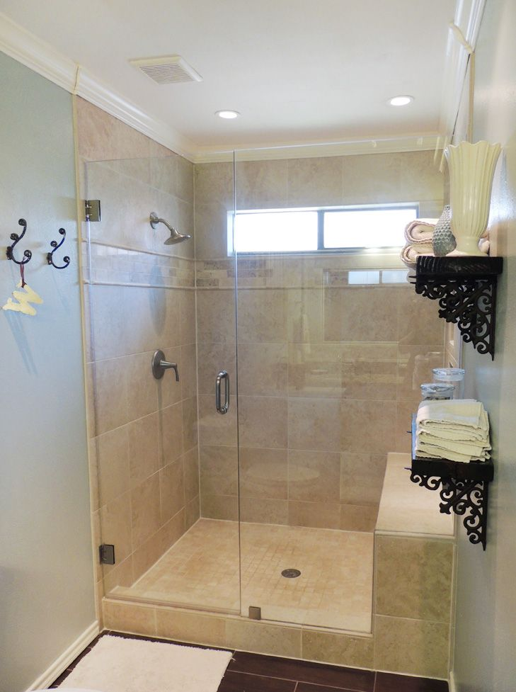 Oversized shower with wall-to-wall travertine-look tile and frameless shower door