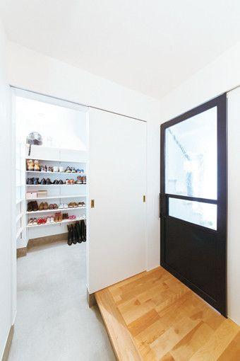 アンティークガラスを嵌めこんだネイビーのドアがおしゃれな玄関。シューズクロークのドアを手前に引けば、たくさん並んだ家族の靴を目隠しできる。