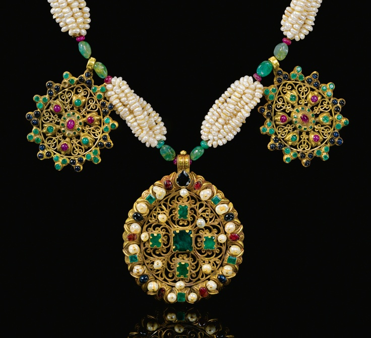 A GEM-SET AND SEED PEARL GOLD NECKLACE (TAZRA), MOROCCO, 18TH CENTURY composed of three hanging sections on a seed pearl necklace, separated by two cylindrical elements with enamelled floral motifs, the hanging roundels of gold-filigreework set with gems, with tiger's stone inset clasp
