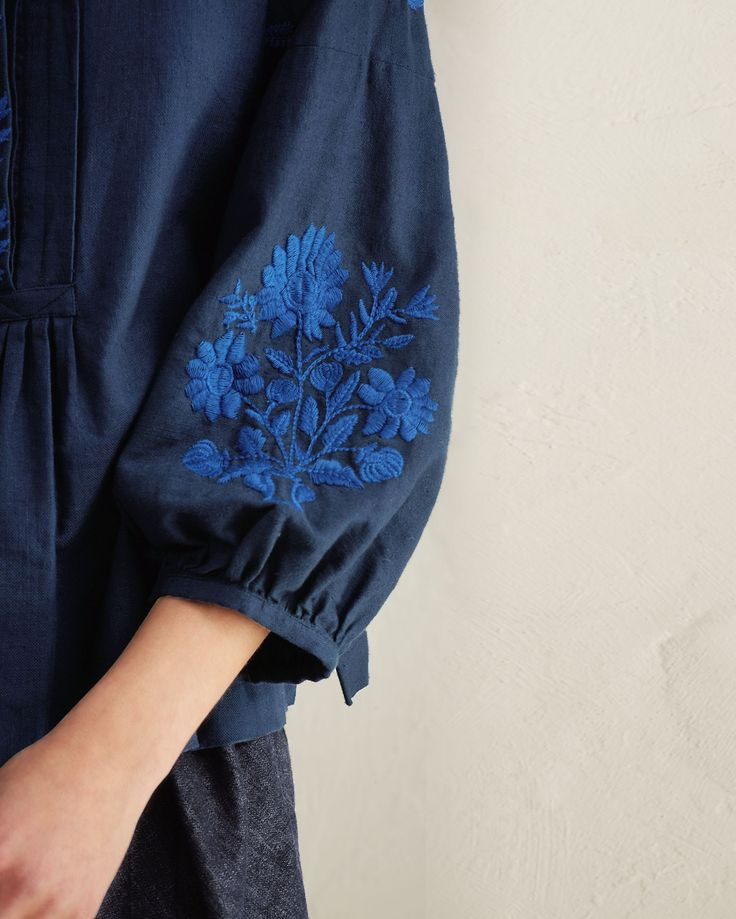 Hand embroidered cotton khadi. Button placket with gathers below. Bracelet-length balloon sleeves. Split hem.