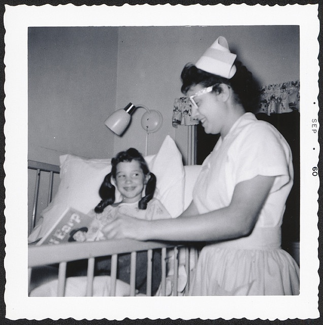 A sweetly bespectacled nursing student reads a young patient a bedtime story in this heartwarming shot from 1960. #nurse #vintage #hospital #1960s #retro #sixties