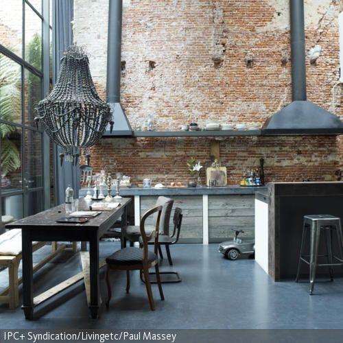 Der große Essbereich im Industrie-Chic wirkt gerade durch die gewagten Zusammenstellungen der Materialien, Metall und Holz, und der Möbel modern und  …
