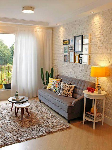 Quem disse que o cinza não pode ser alegre? O sofá cinza foi combinado com um ambiente branco de decor colorida, a parede de tijolos quebra a seriedade.