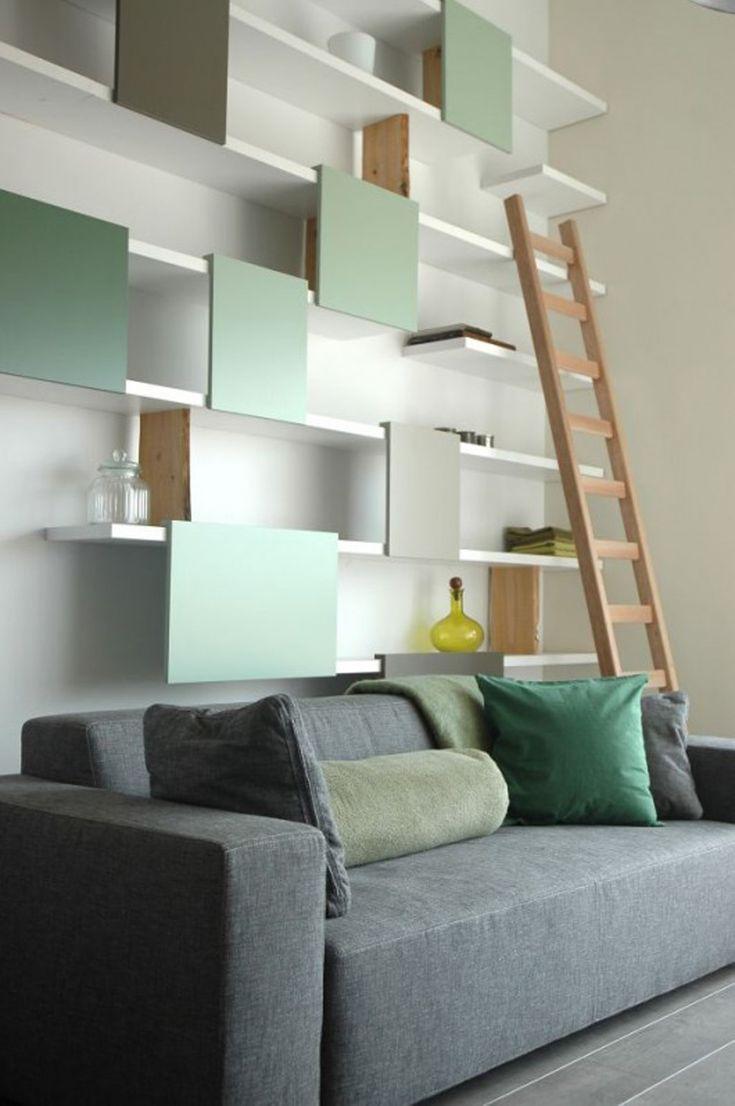 Stilvolle schicke grüne und weiße hängende moderne Wandregale montiert an der Wand hinter dem zeitgenössischen grauen Sofa