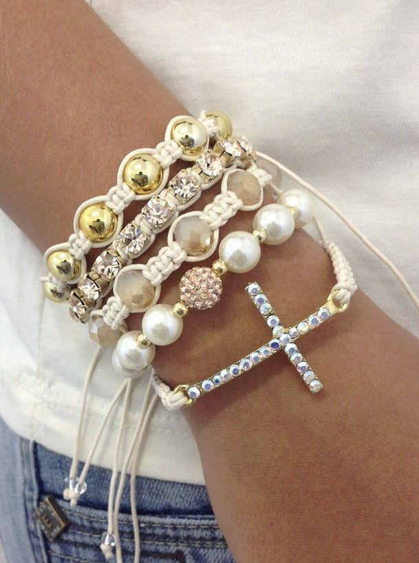 D4000S4700    Kit de pulseiras shambalas, com cricifixo, strass e cristais, confeccionada com cordão encerado na cor cru, composto de 5 pulseiras:  - 1 pulseira de crucifixo dourado com strass cristais com efeito aurora boreal e cristais facetados de 8 mm na cor cristal  - 1 pulseira de pérolas d...