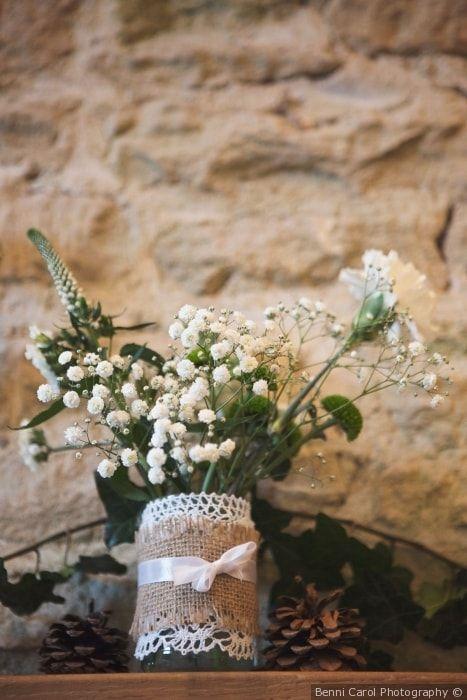 Barattolino decorativo con fiori freschi, pizzo, raffia e nastro in seta con pigne per un matrimonio shabby chic
