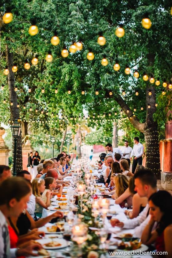 Outside wedding reception. Guests sat under strings of bulb lights and trees at tables topped with pillar candles. Click by: Pedro Bento #Weloveweddings #AWP #PaulaandKarina #Weddings #Readytowed #DestinationWeddings #reception #inspiration