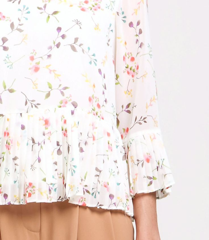 Bring out the florals with this patterned blouse. It features an open back, inner lining, a pleated peplum hem and sleeves. Style this with camel peg leg trousers for a pretty look.