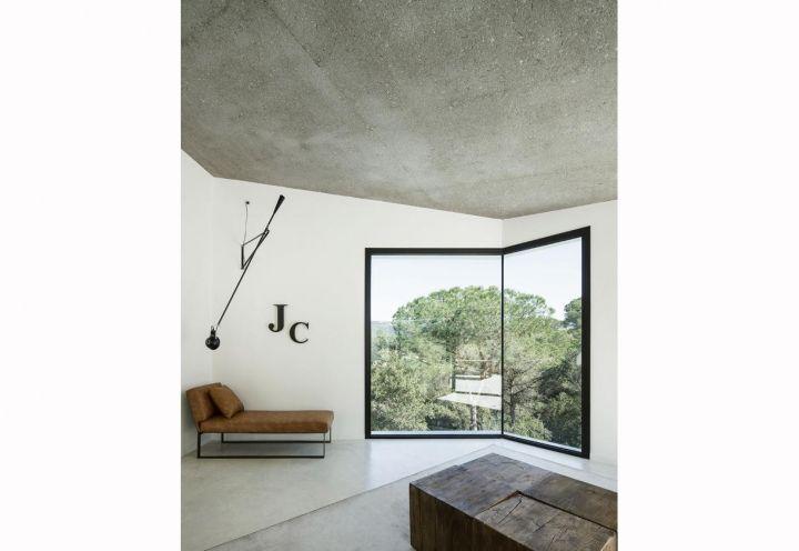 Un angolo del soggiorno della casa catalana di Llavaneres. Accanto alla finestra una chaise longue con struttura in ferro rivestita in pelle marrone, sormontata da una lampada a parete modello 265 di Flos