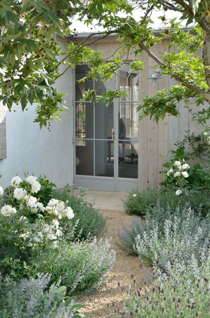 What a beautiful soothing elegant white/silver garden with touches of soft blues/purples under mature tree..The meandering fine gravel path makes for an enticing enviable landscape