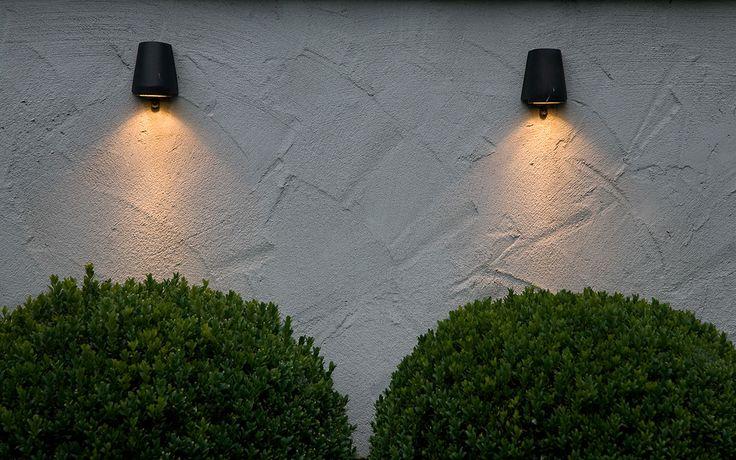Gestuukte muren met verlichting van Royal Botania. Onder de verlichtingsarmaturen staan grote aardewerk bruine potten met Buxusbollen.