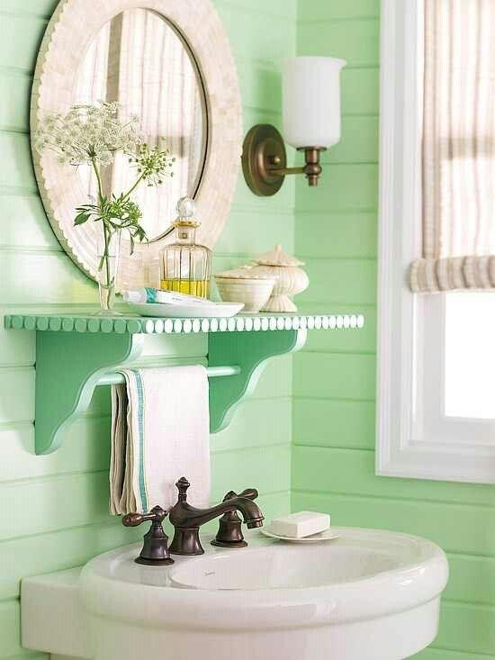 Cottage Bathroom: white, seafoam, sconces, oval mirror, shelf above pedestal sink.