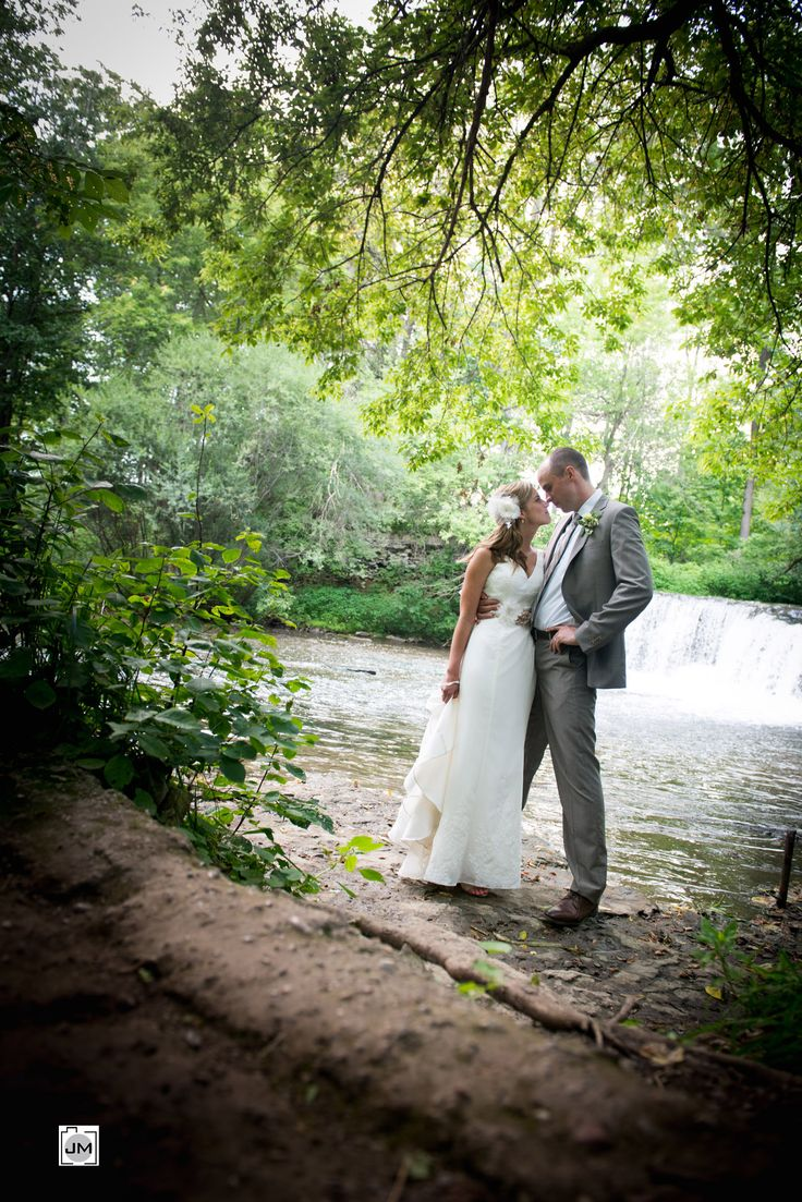 Lynn River Falls - Port Dover Wedding - Bride and Groom beside a waterfall in Port Dover, Ontario. Heart shaped leaves frame them. Bride and groom nose to nose!