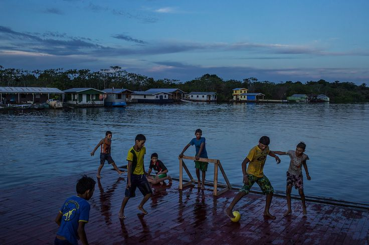 Catalão, Brazil - June 27, 2014: Boys play soccer on the dock of a restaurant at dusk in Catalão floating community, near Manaus, in the Amazon basin. CREDIT: Photo by Mauricio Lima for The New York Times