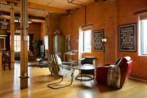 Diese industriellen Wohnzimmer verbindet kunstvoll die exponierten Wand seiner hölzernen Befestigungen, industriellen Elementen. Foto von AMR Innenarchitektur & Ausarbeitung Ltd.