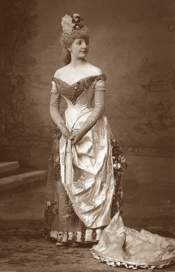 1880s. Off-shoulder evening(?) dress. Bustle fashion and long train and opera gloves. High hair updo. Beautiful details <3