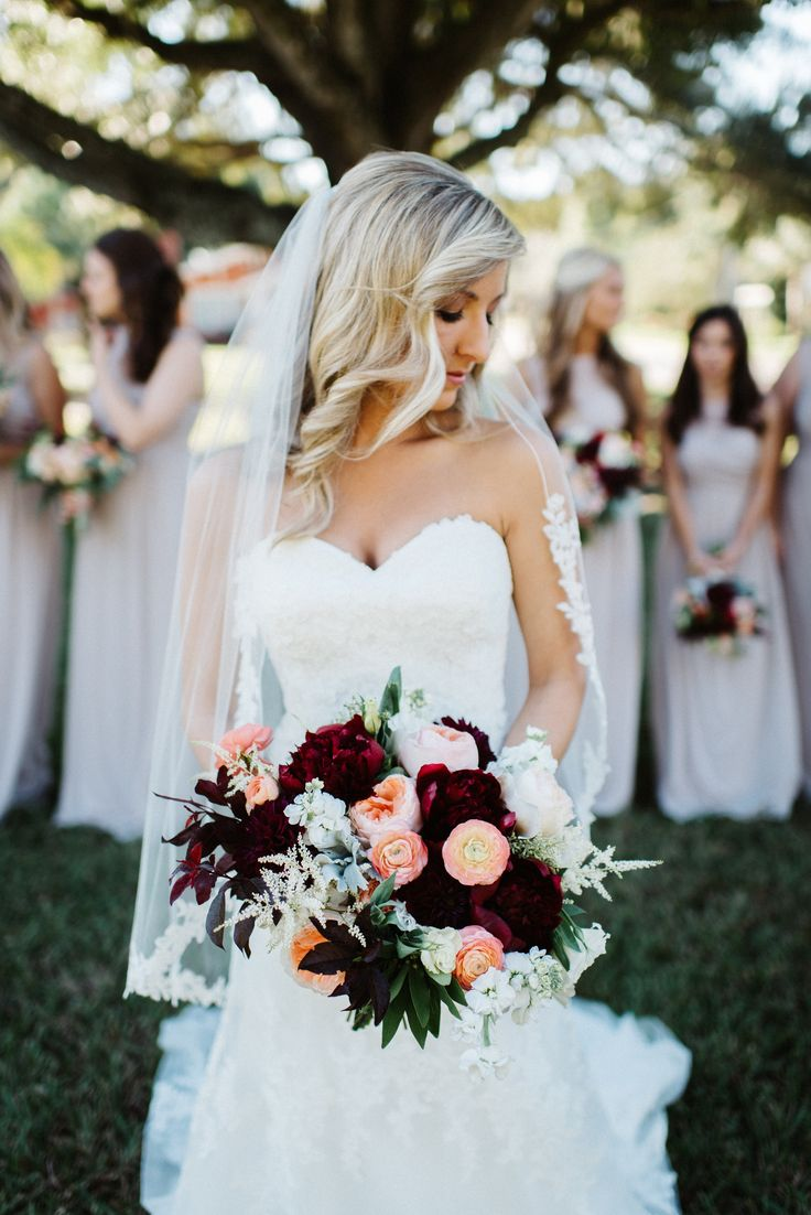 loose and unstructured clutch bridal bouquet of red charm peony, juliet garden rose, white stock, burgundy dahlia, ivory astilbe, peach ranunculus, seeded eucalyptus, dusty miller, white lisianthus & lemon leaf.