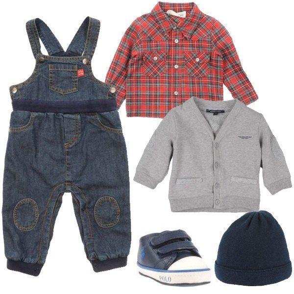 Un outfit per piccoli ometti composto da una salopette in jeans abbinata ad una camicia in cotone a quadri sui toni del rosso. Un cardigan grey con bottoncini e taschine. Una scarpina sportiva in pelle e un cappello in cotone blu.