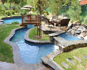 A bridge, a lazy river, a waterfall, and cozy nooks for seating all combine to create a playful, yet relaxing outdoor living environment. The lovely landscaping is incorporated into the entire setting to make this pool in Valencia even more inviting.