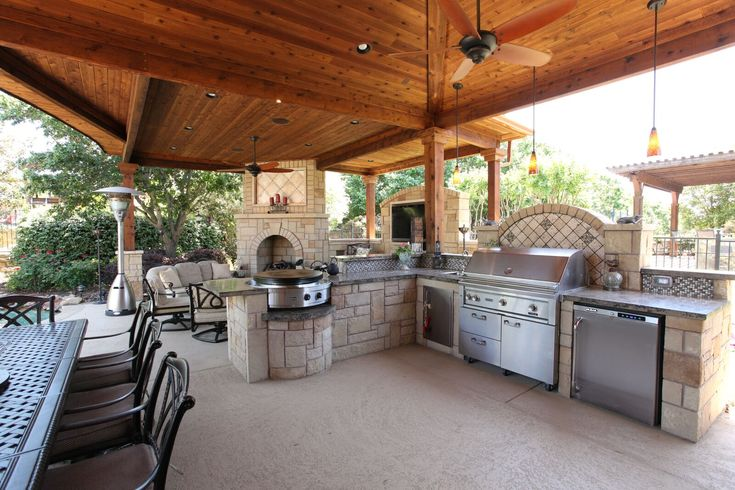 This outdoor kitchen features all the conveniences of an indoor one: grill, refrigerator, sink, and EVO griddle. By Outdoor Signature in Argyle, TX