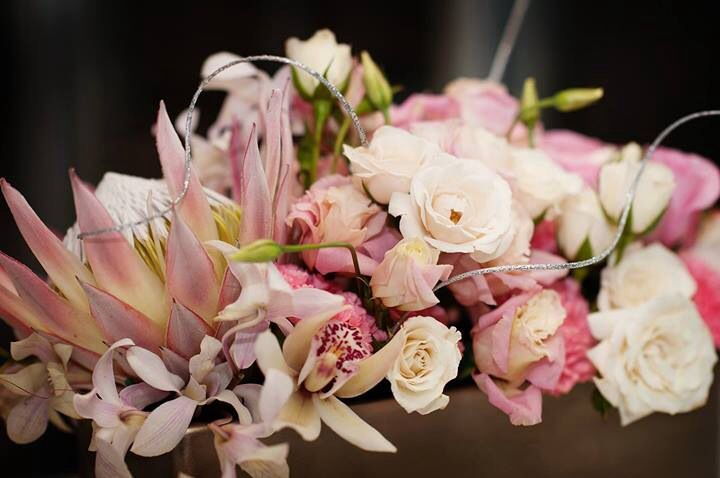 Blush centerpiece for wedding with protea, majolica spray roses, white cymbidiums. #mainstreetflower in Parker, co