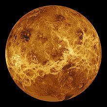 A false color image of Venus: Ribbons of lighter color stretch haphazardly across the surface. Plainer areas of more even colouration lie between.