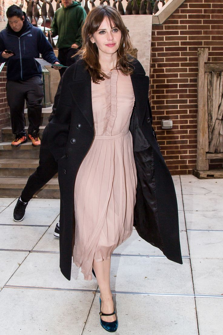 28 November Felicity Jones wore a pretty nude dress with a black coat for an outing in New York.