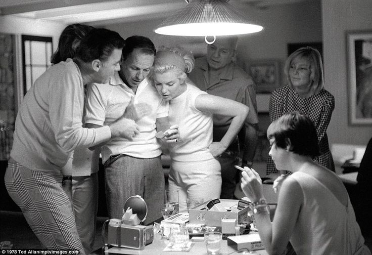 Frank Sinatra and Marilyn Monroe (center) cuddle up while having drinks with Peter Lawford...