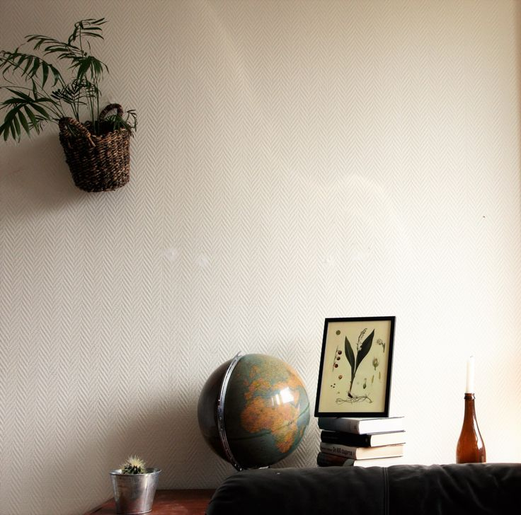 Vintage globe, small cactus and an old giant beer bottle with a single white candle in it. Green palm-plant mounted on the wall. On the hipster bookstack we find the beautiful lily of the valley-print in a minimalistic frame.